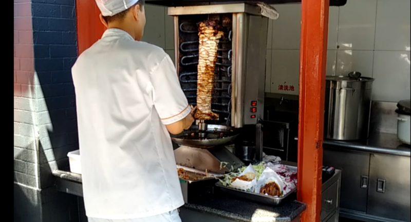 Китайский шаурмайстер срезает мясо с шампура на рынке Wangfujing Snack Street в Пекине.